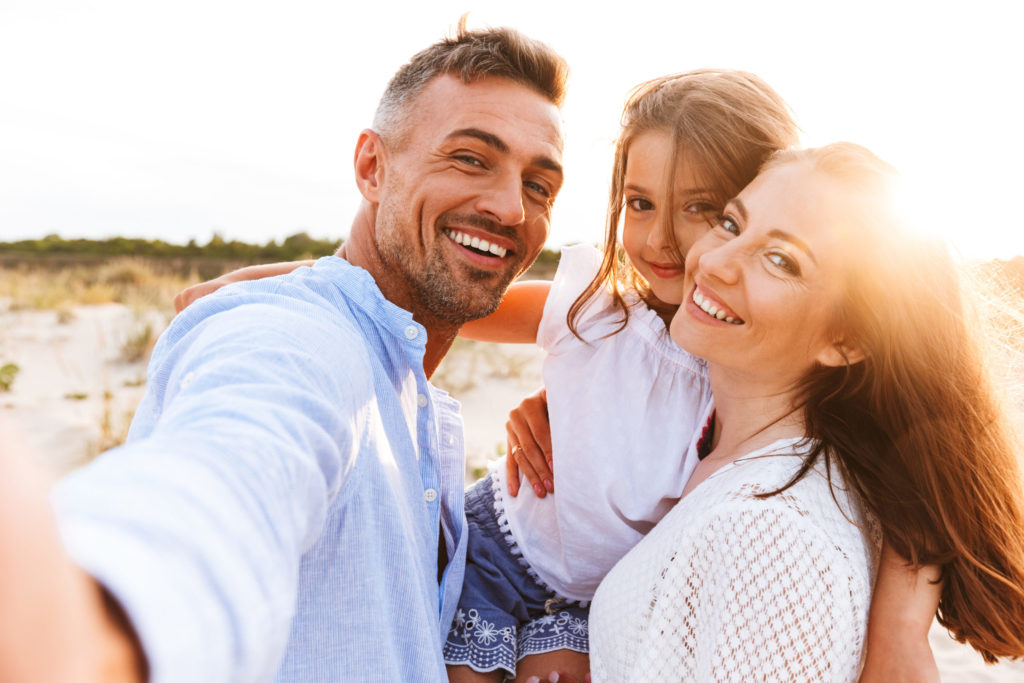 Happy family takes a selfie together on the beach during a vacation using paid time off.