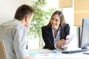 A smiling benefits administrator or wealth advisor shows an employee their compensation package.